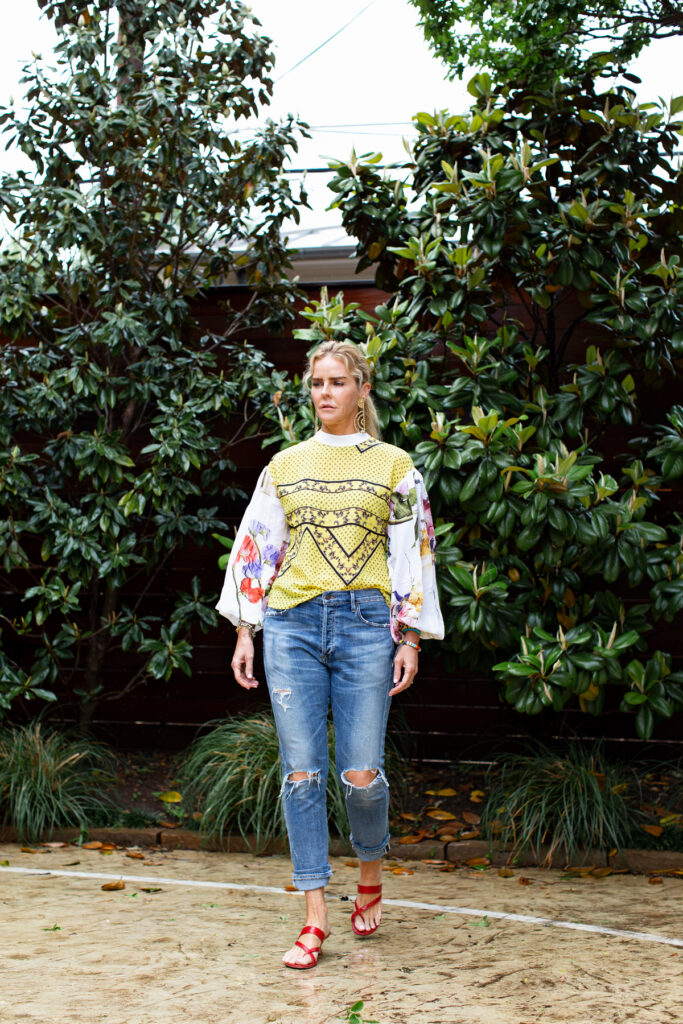 woman wearing yellow big sleeve Ganni blouse, ripped boyfriend jeans in front of magnolia trees