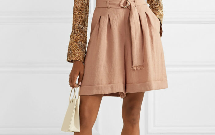 Model wearing a snake print button up blouse with long wide leg linen shorts holding a white mini handbag and wearing b