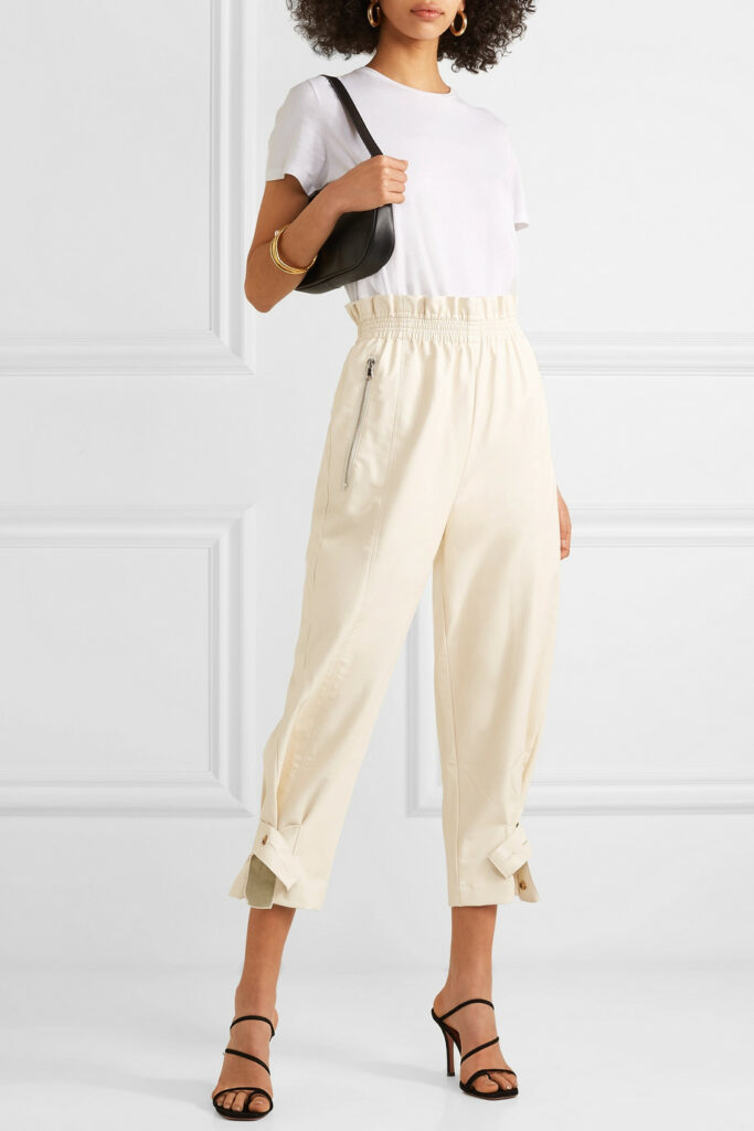 girl in white tee and cream colored faux leather paper bag pants carrying a small black shoulder bag with which gold arm bangle and strappy sandals.