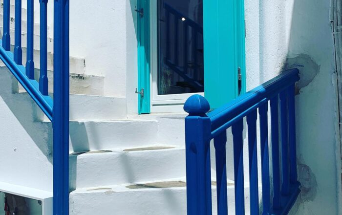 white washed staircase with brilliant blue railing and aqua blue window shutters in Mykonos, Greece