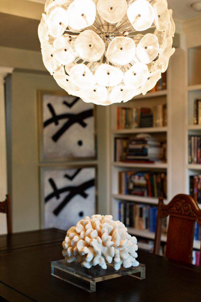 Lalique crystal chandelier with large white coral on a Plexiglas base with abstract art in the background and bookcases.