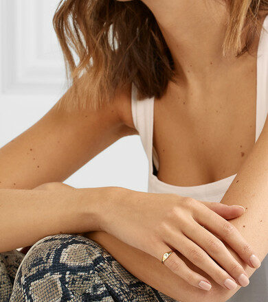 Woman with a tank top and arms crossed displaying a dainty initial pinky ring