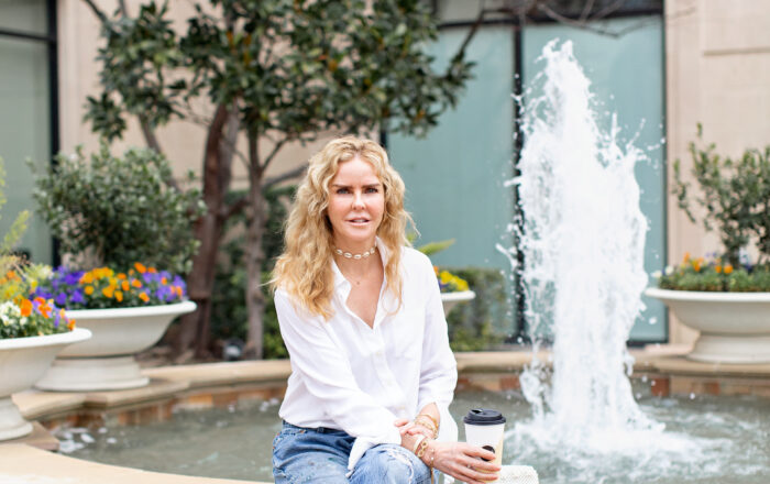 girl sitting on the side of a fountain holding a McDonald's latte cup wearing Vintage Levis 501 and a white silk button up blouse with pink Balenciaga knife mules.