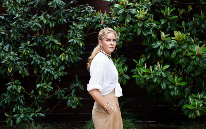 Woman standing by holly trees in white cotton voile blouse tied at the waist and high waisted beige wide leg pants