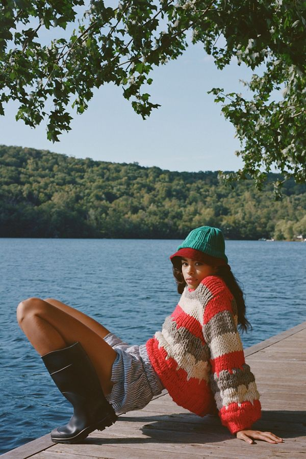 Girl on a dock with chunky knit red beige and white sweater and knit hat with stripped shorts and rain boots on.