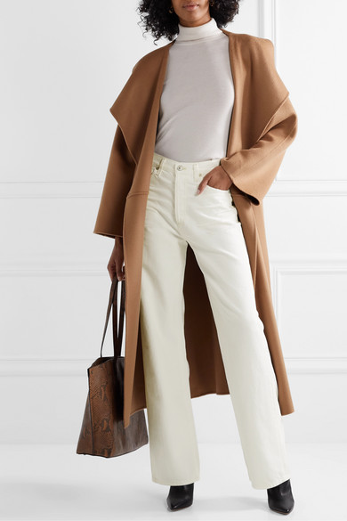 Woman wearing Citizen of Humanity white wide leg jeans white turtleneck and a long camel wrap coat with black boots and carrying a tan tote bag.