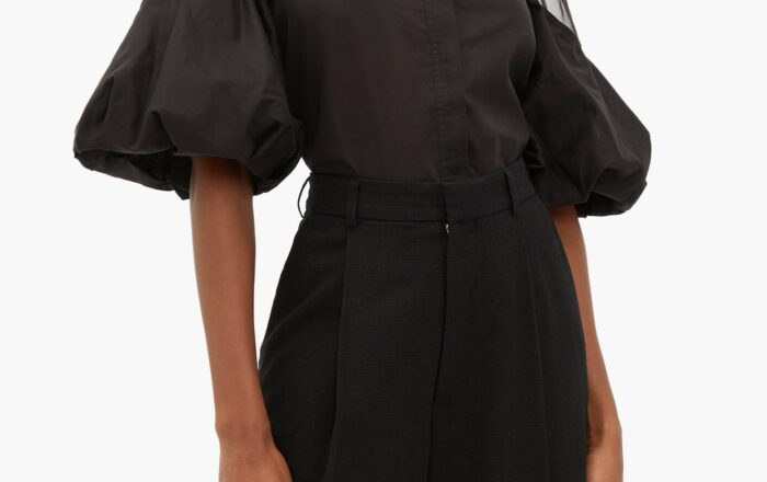 model wearing a black puff sleeve blouse with sheer organza on the top of the blouse and sleeve