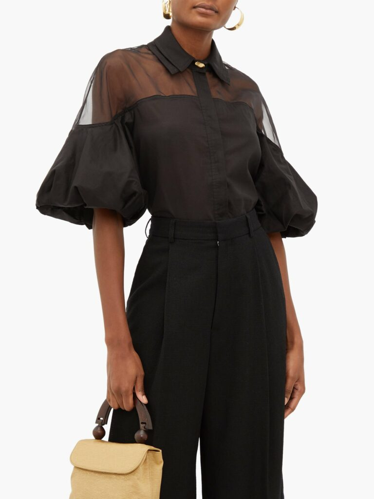 model wearing a black puff sleeve blouse with sheer organza at the top of the body and top of sleeve.