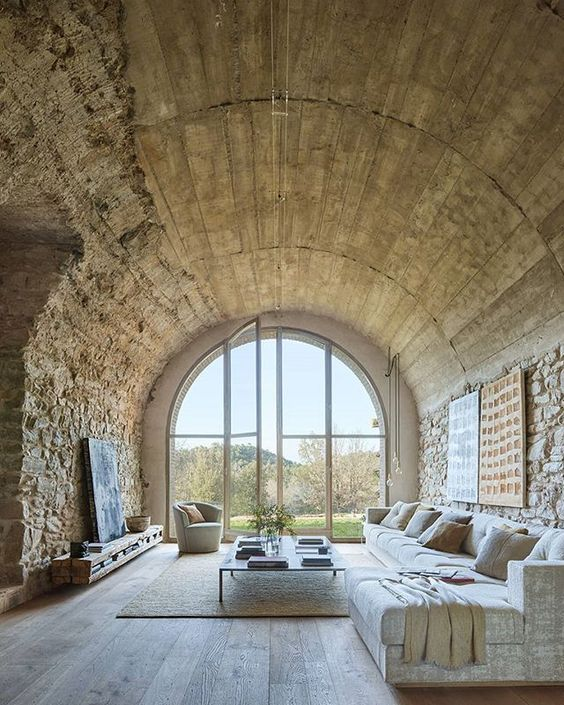 large white leather couch and coffee table in a domed stone room with a large arched doorway