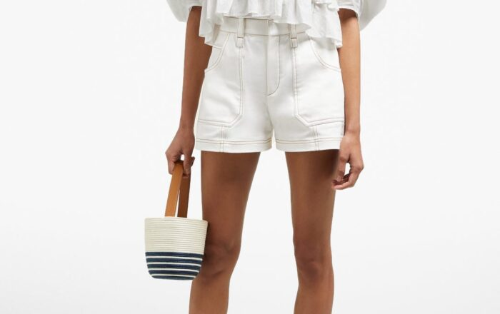 model wearing a white Rhode Elodie blouse with white shorts with contrasting brown stitching and carrying a small round striped basket purse with brown leather strap wearing gold slip on sandals