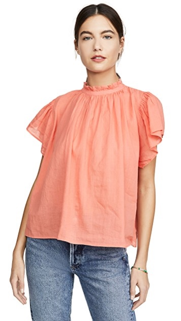 dark haired model wearing a peach colored high ruffle neck flutter sleeved blouse by Birds of Paradis