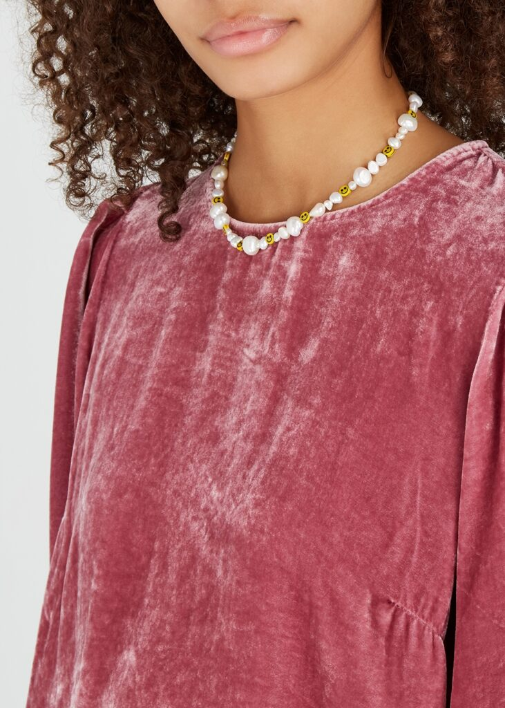 African American model with a pink velvet top and a pearl necklace with smiley face beads