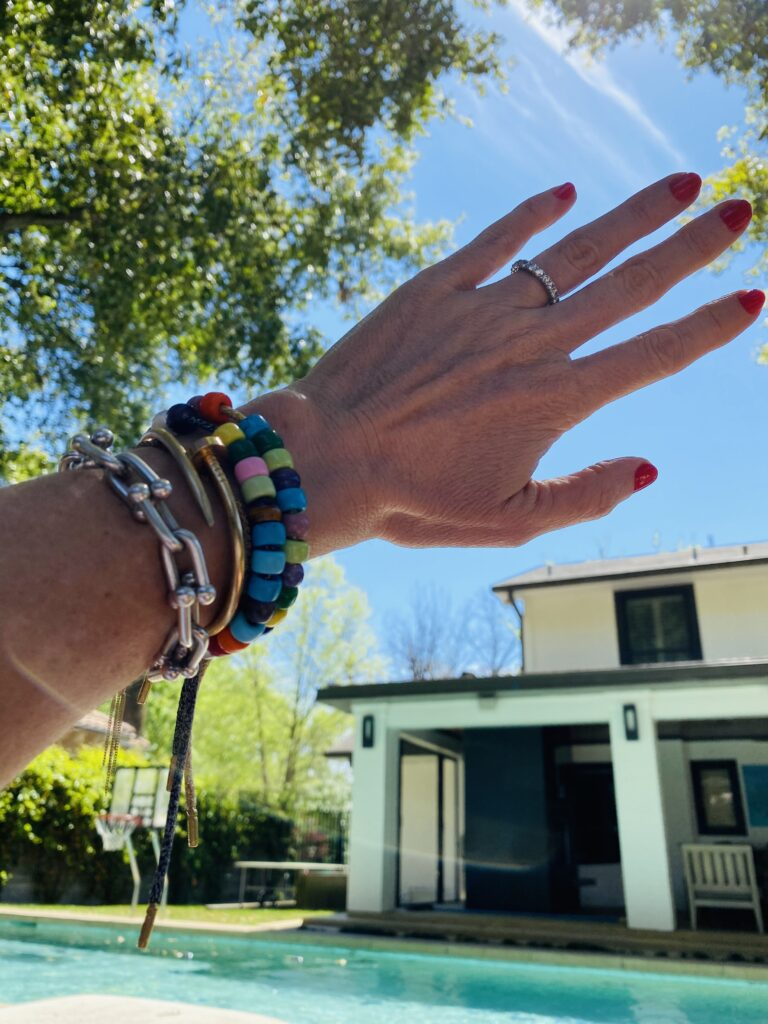 Laura McBride's hand held in the air with 2 Carolina Bucci Forte bead bracelets, Cartier Juste un Clou bracelet and Tiffany Hard Wear silver bracelet.