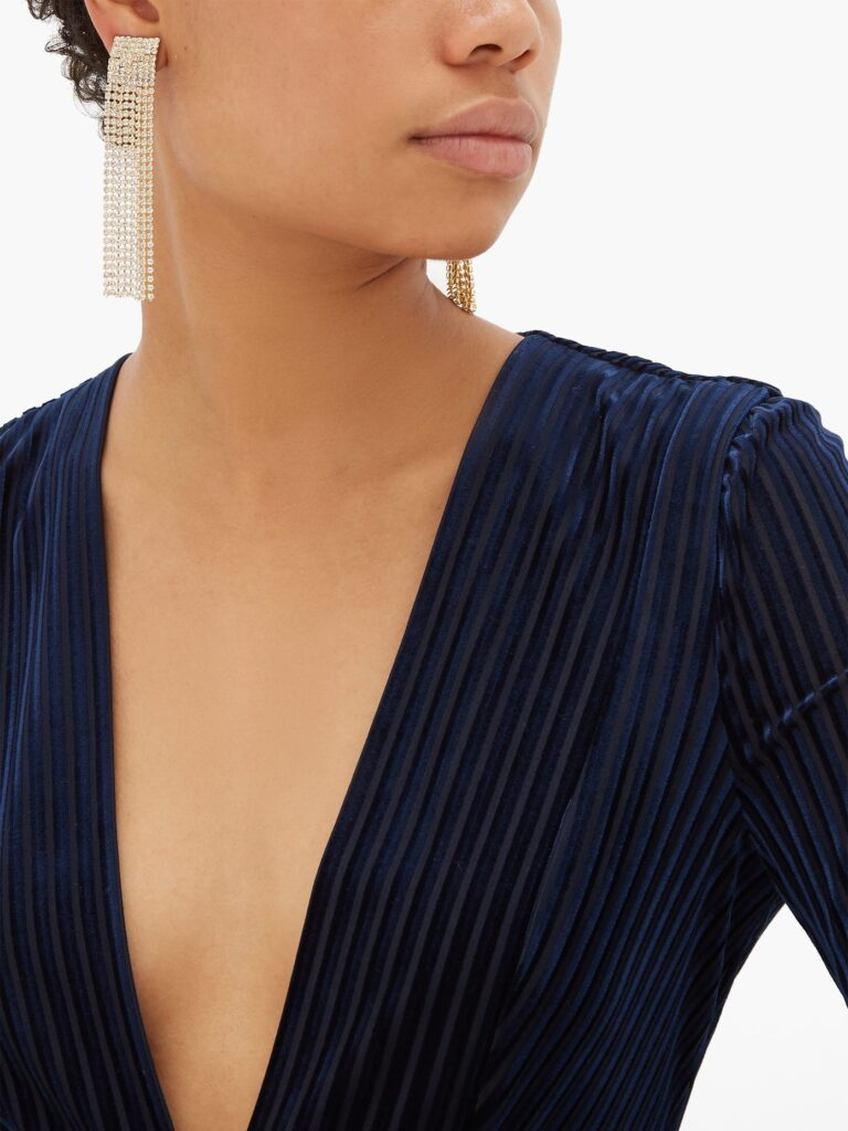 Rosantica crystal fringe earrings on African American model with navy deep V neck sweater