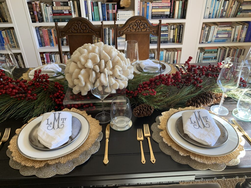 dining room table with white coral centerpiece  set with gold flatware, gold charger plates, white plates with silver rim, sliver salad plate and a folded monogramed linen napkin