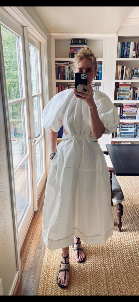 Laura McBride wearing a white Aje puff sleeve dress with black Chanel gladiator sandals standing in dining room with bookshelves behind her.