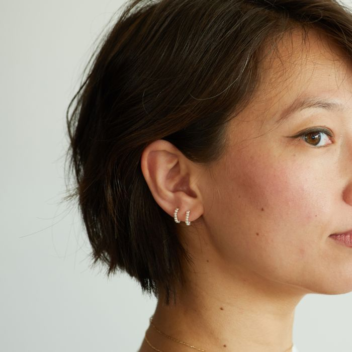 Asian model with short bobbed black hair wearing 2 small pearl hoops in one ear.