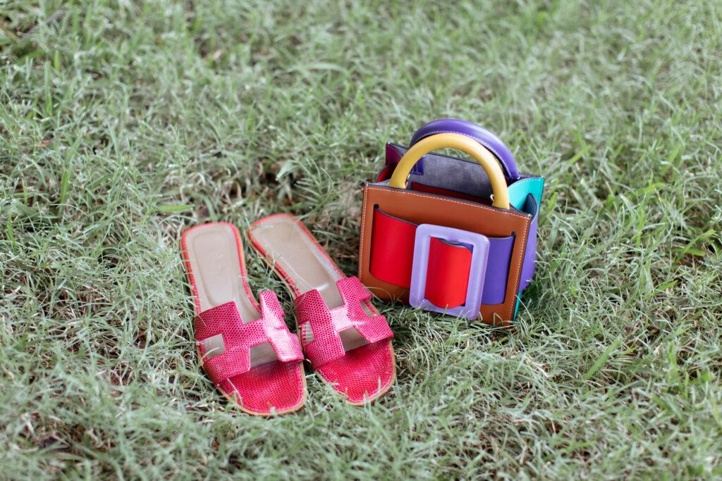Raspberry colored snakeskin Hermes Oran sandal next to a Boyy multi colored handbag arranged in the grass