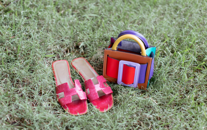 Raspberry colored snakeskin Hermes Oran sandal next to a Boyy multi colored handbag arranged in the grass