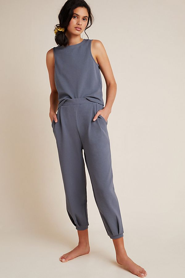 Dark haired model wearing Lourdes slate grey tank and matching lounge pants barefoot.