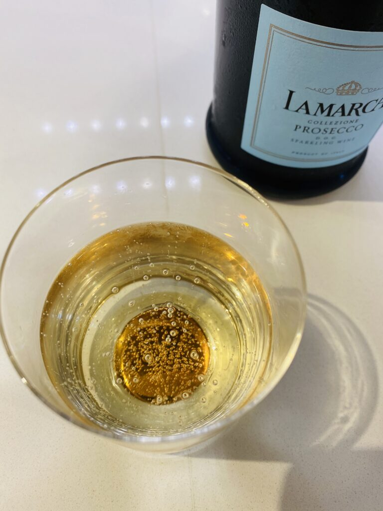 LaMarca proceso bottle in background with a glass of full of Prosecco with bubbles at the top