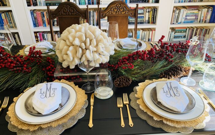 dining room. table with wihite coral on a plexiglass stand as the centerpiece with gold charger plates, white silver rimmed dinner plates, silver salad plates, monogramed linen napkins folded and placed on top of silver salad plate with gold flatware