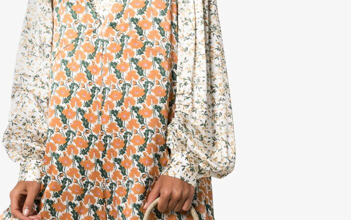 model wearing a orange and grey floral dress with white floral puff long sleeves holding a top handle woven bucket bag with woven bead embellishment