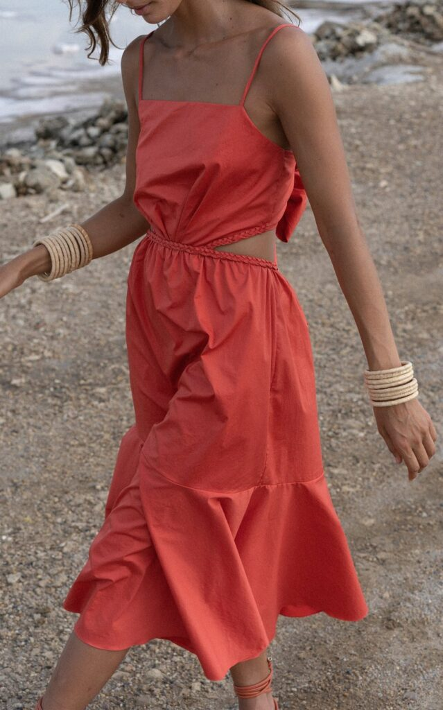 model walking on the beach in a red Johanna Ortiz cut out midi dress with bone colored bangles stacked on both arms and a thin gold chain